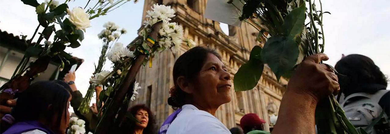 A woman holds flowers as she attends a peace march, Bogotá, Colombia.