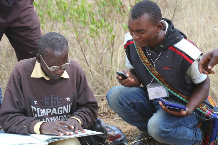 Gaspar Bangi, right, cross-checks data with an adjudicator from the Kiponzelo field surveying team