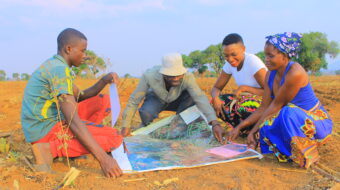 men and women look at land map